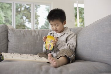 Smiling Boy  on Sofa with Coloring Book