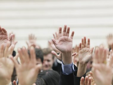 Crowd of people raising hands