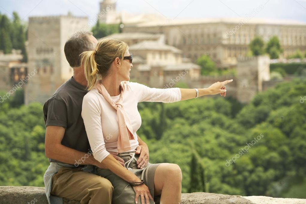 Tourist Couple sitting on Wall