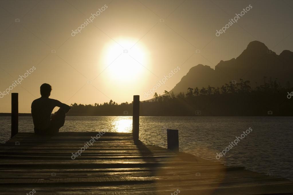 Man sitting on dock by lake