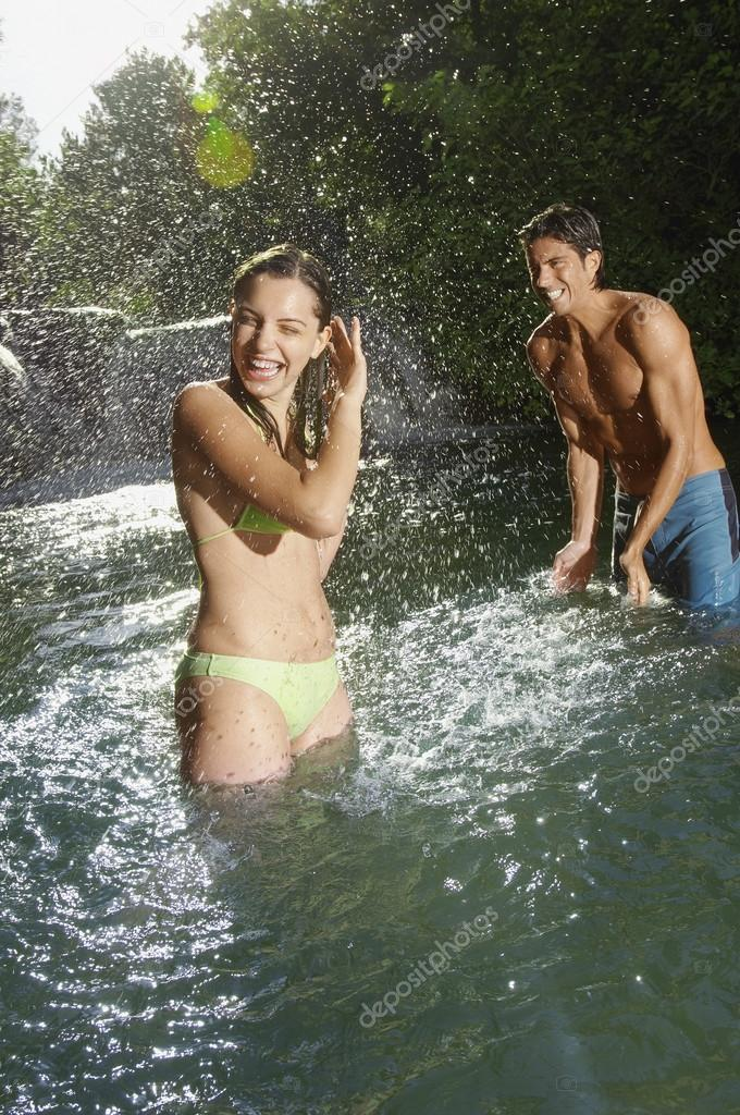 Man splashing water on girlfriend