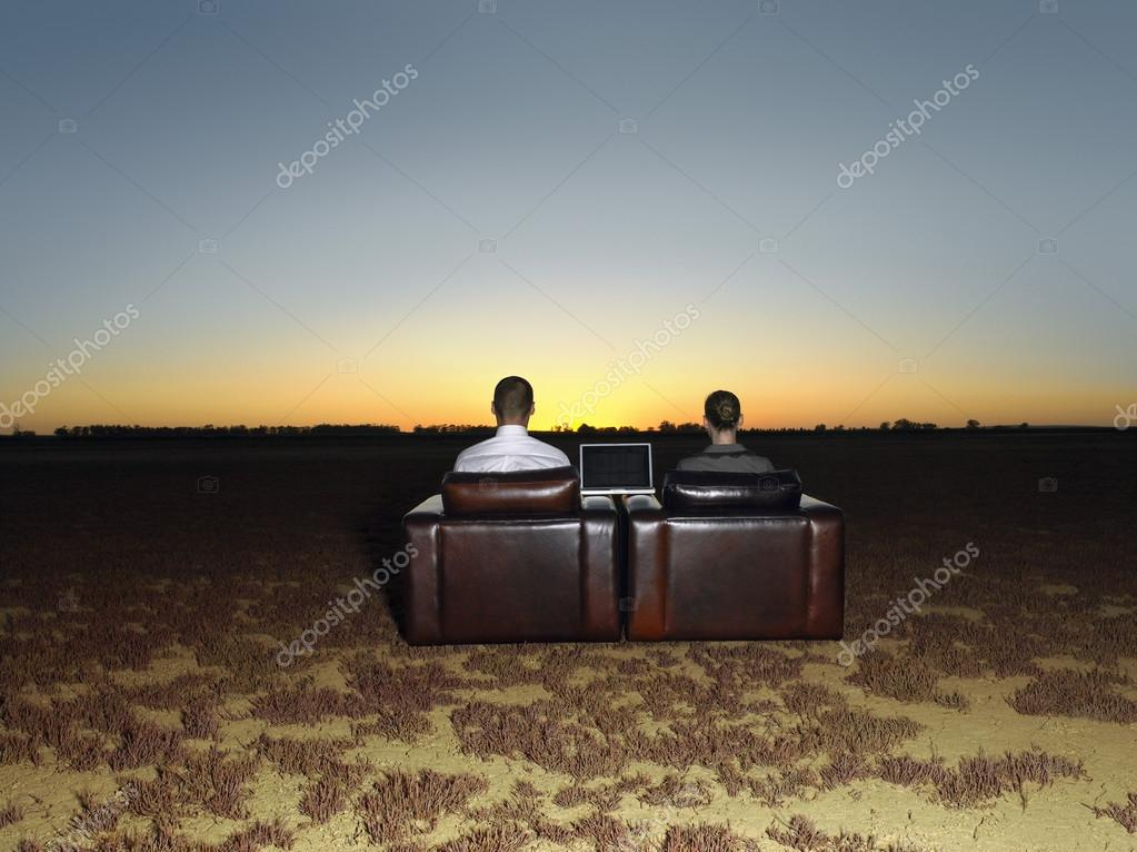 Business people in arm chairs at sunset