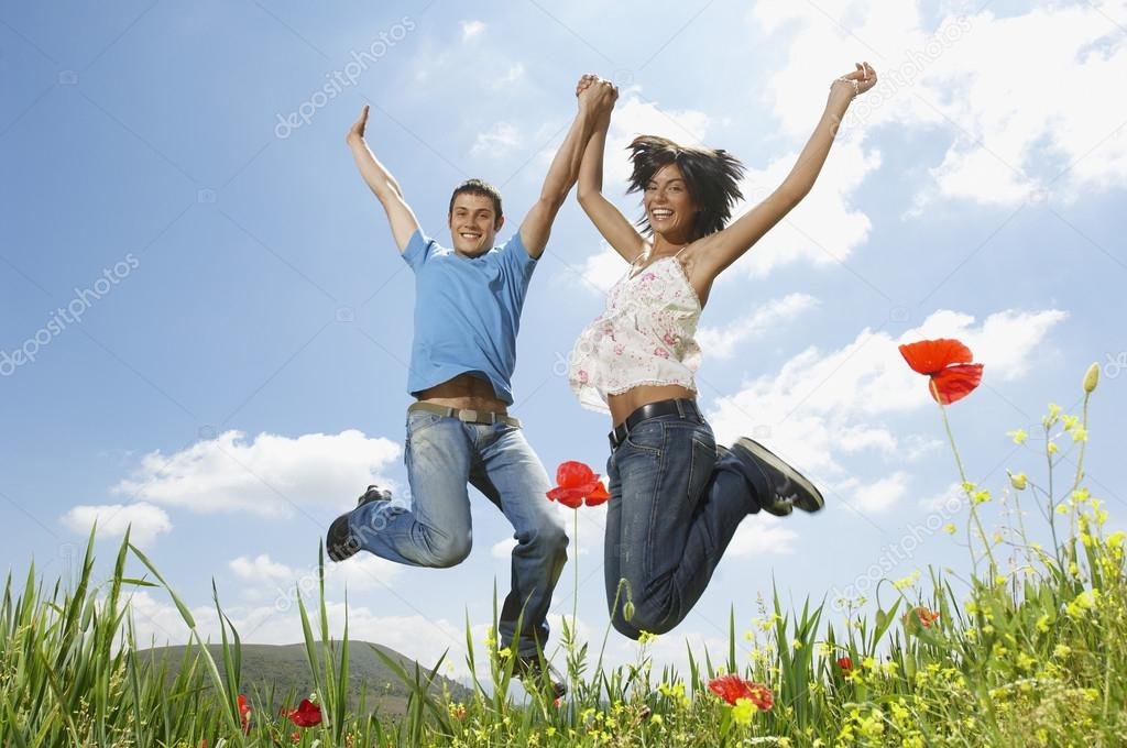 Couple jumping in meadow