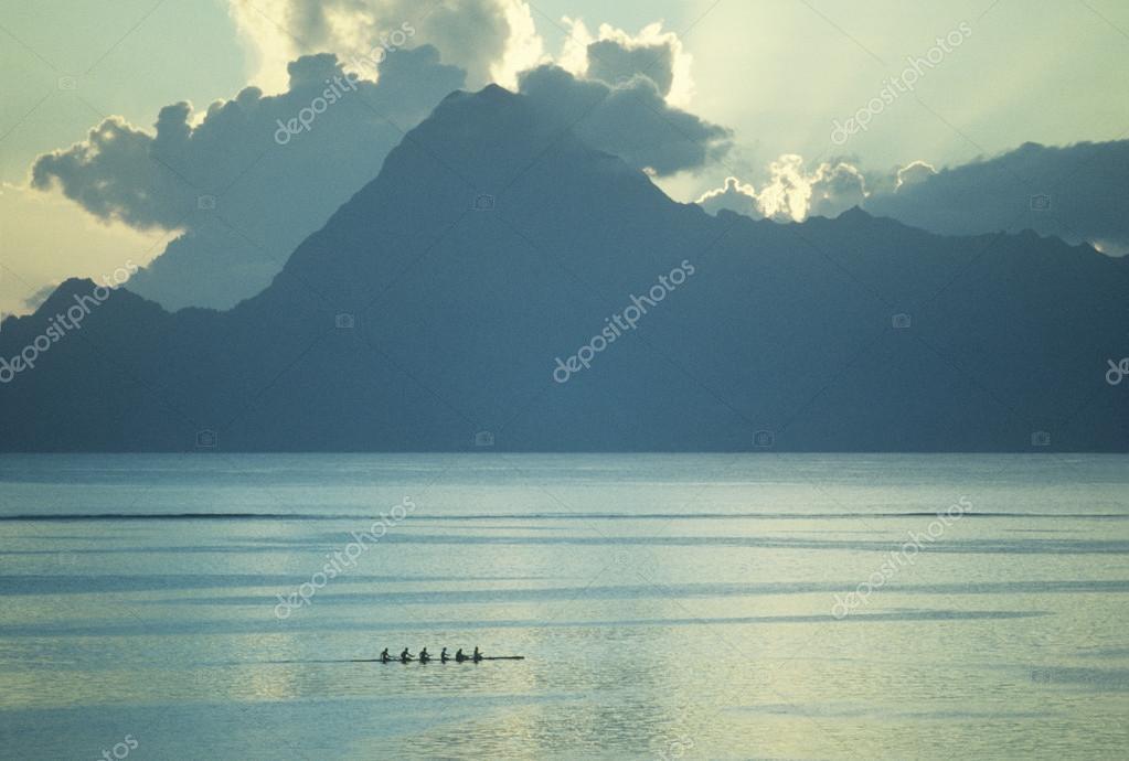 Mountain silhouette upon river sunrise
