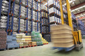 Photo Speeding Forklift in Warehouse