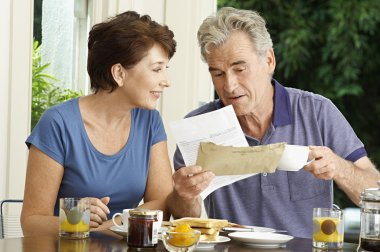 Couple looking at bill over breakfast