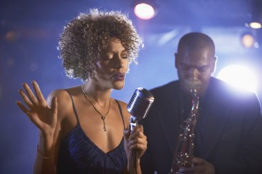 Female singer and saxophonist performing