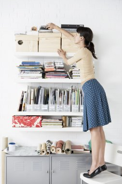 Businesswoman reaching for Shelf
