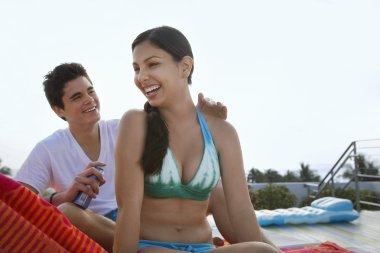 Teenage boy applying sunscreen