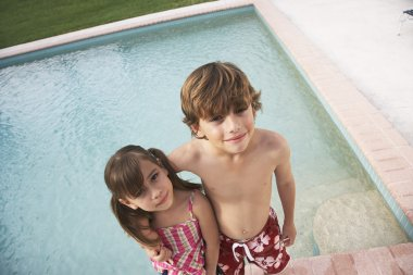 Boy and girl embracing near pool