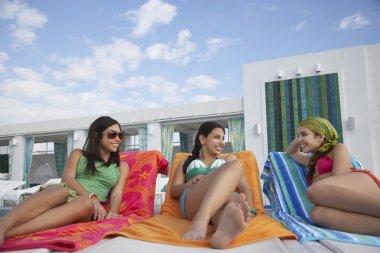 girls  lying on sunloungers