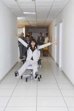Office workers playing on office chairs