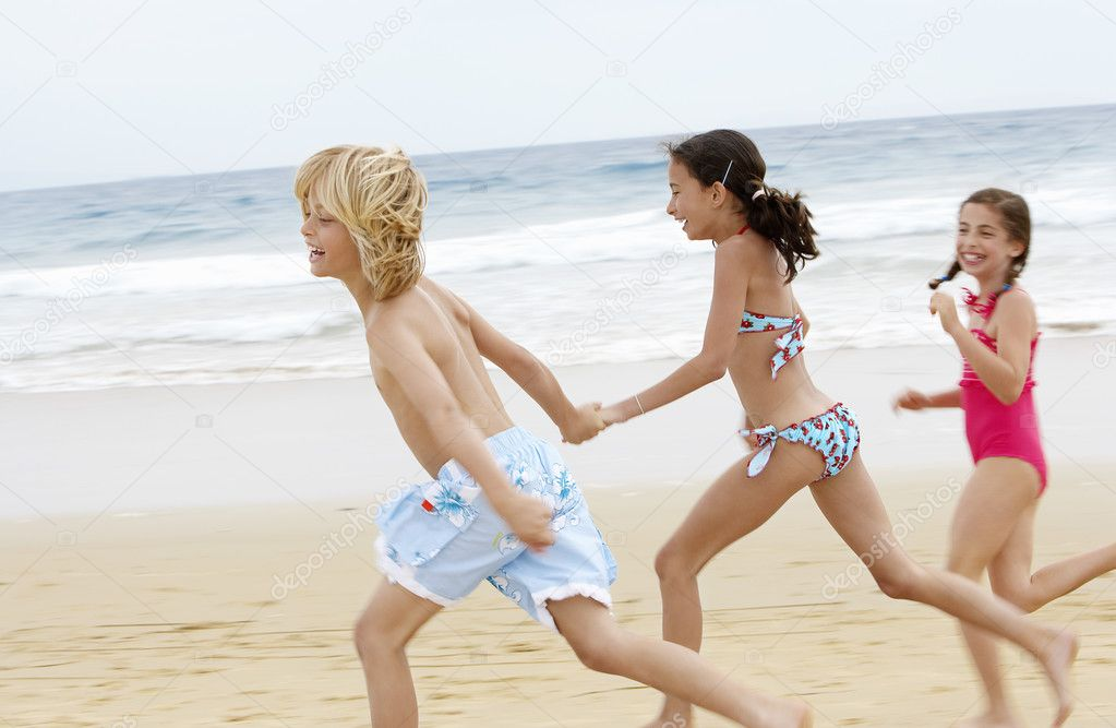 Children  running along sandy beach