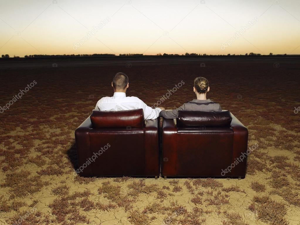 Couple watching sunset sitting in armchairs