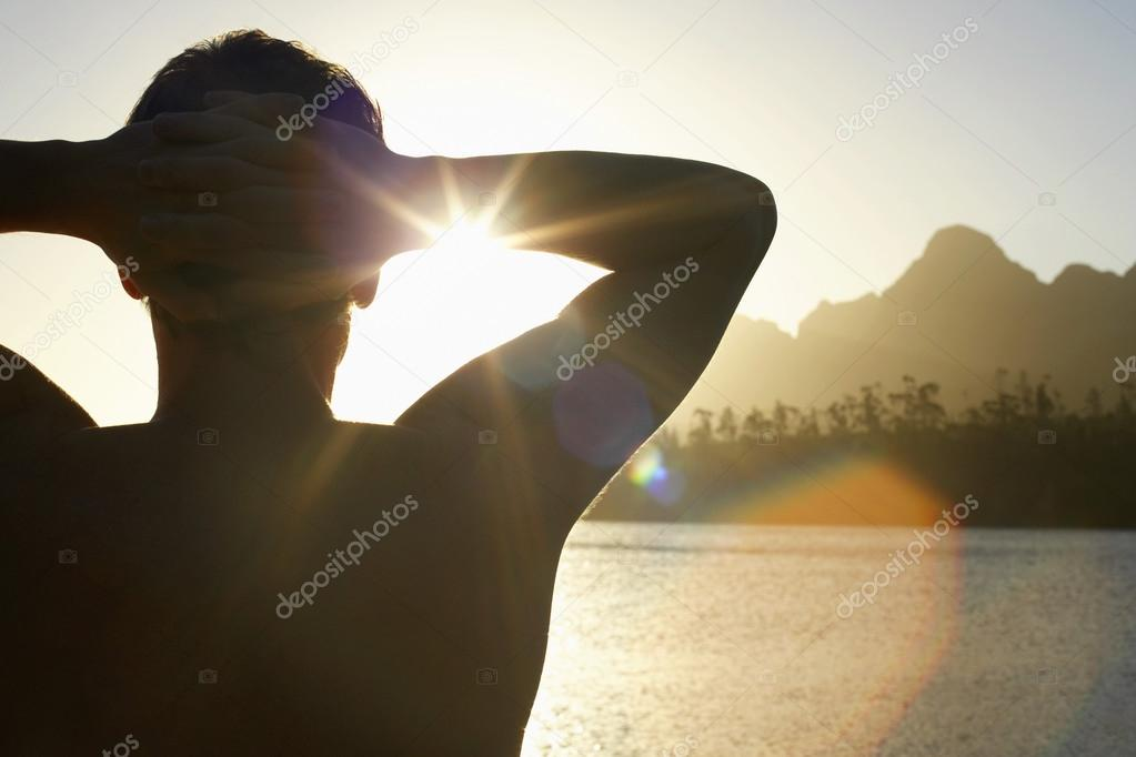 Man by lake with hands behind head