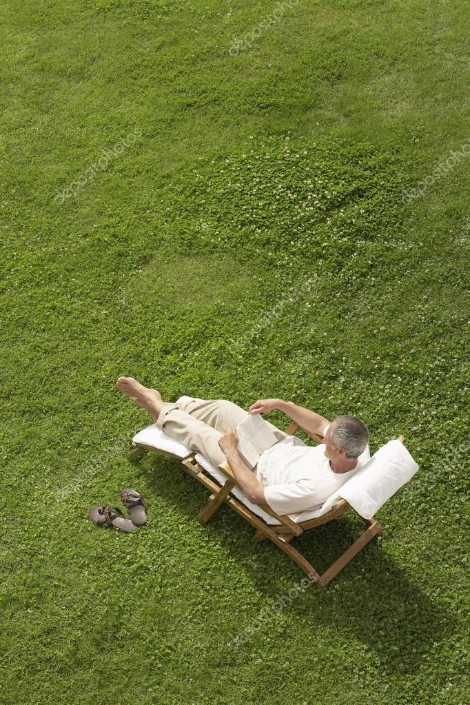 Man in deck chair reading