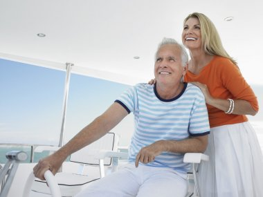 couple at helm of yacht