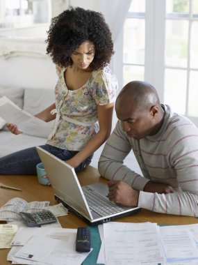 Couple using laptop and holding bills