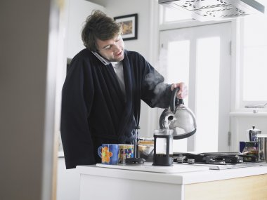 Man using phone in kitchen with coffee