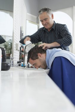 Barber washing head in barber shop