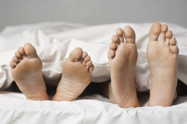 barefoot Couple lying in bed
