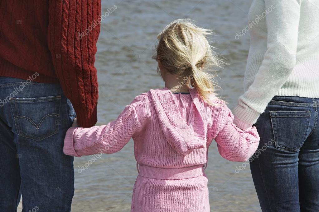 little Girl holding parents hands