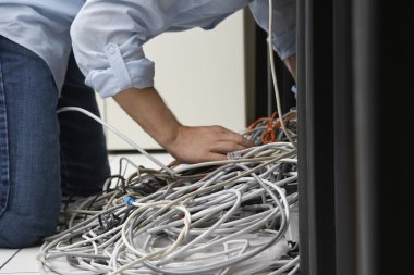 Man working on tangle of computer wires