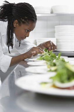 Female chef preparing salad