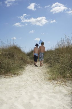 Boys walking in sand dunes