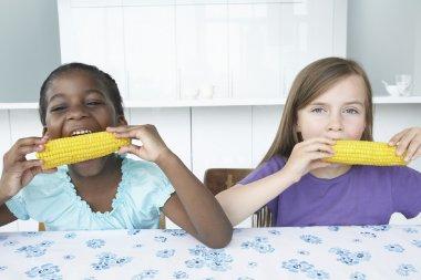Girls Eating Corn Cobs
