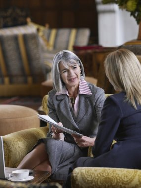 business women in lobby with documents