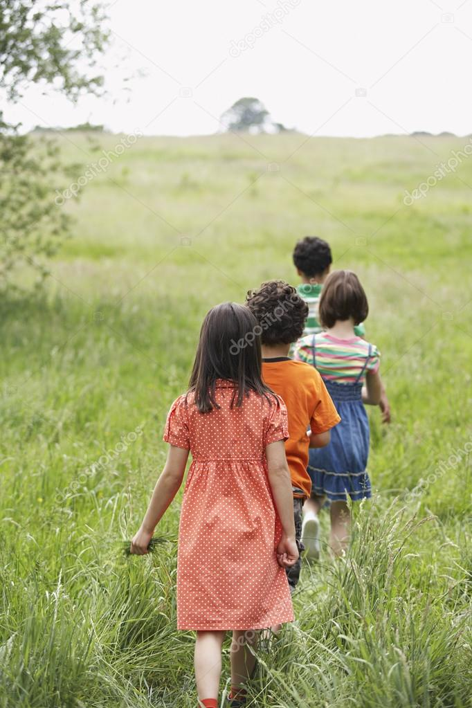 Children Walking Across Meadow