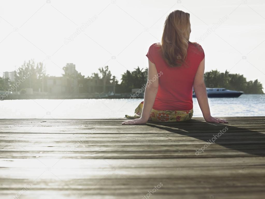 Woman sitting on edge of jetty