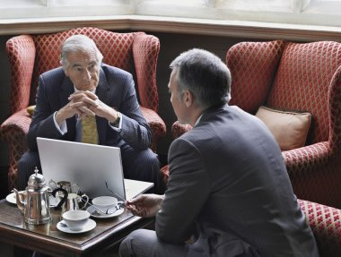 businessmen talking with laptop