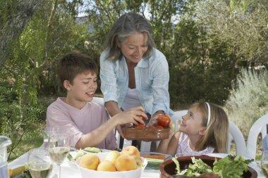 Senior woman serving fruit to children