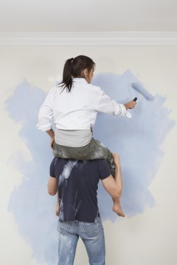Woman riding shoulders of man to paint wall