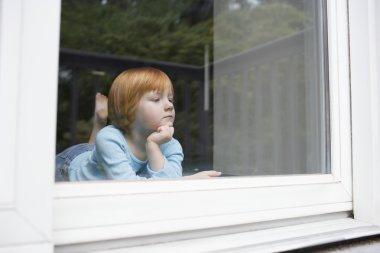 girl looking through window