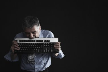 Businessman Biting a Computer Keyboard