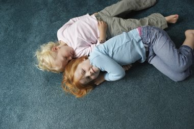 Sisters lying on carpet