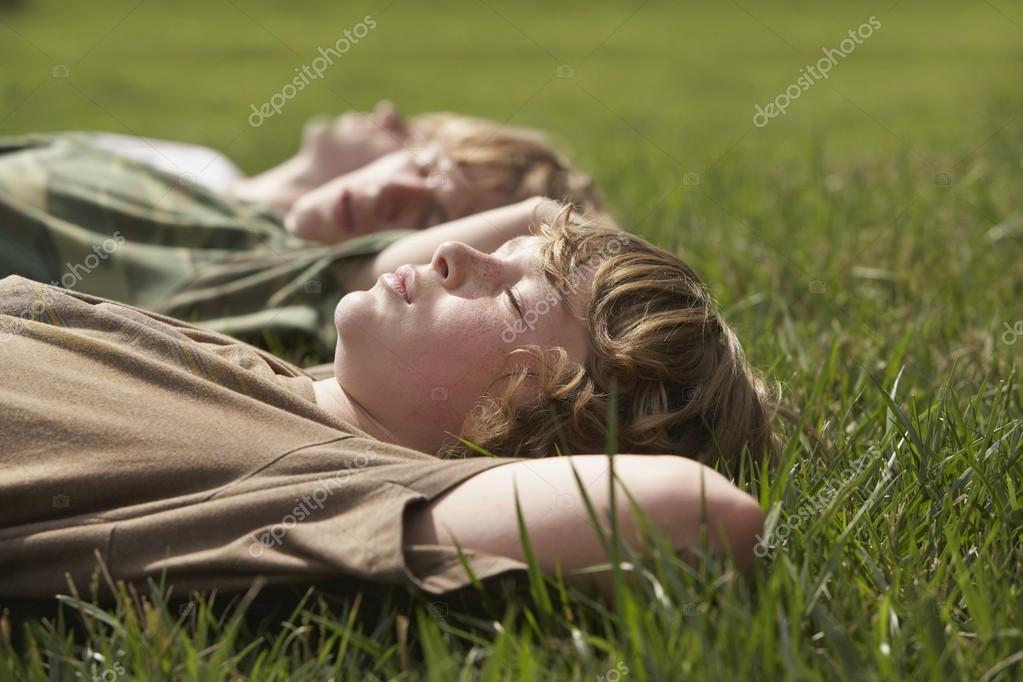 Three teenage brothers  on grass