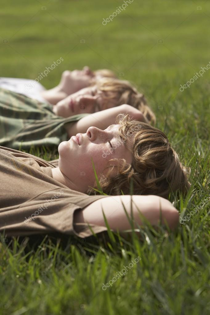 Brothers lying on grass