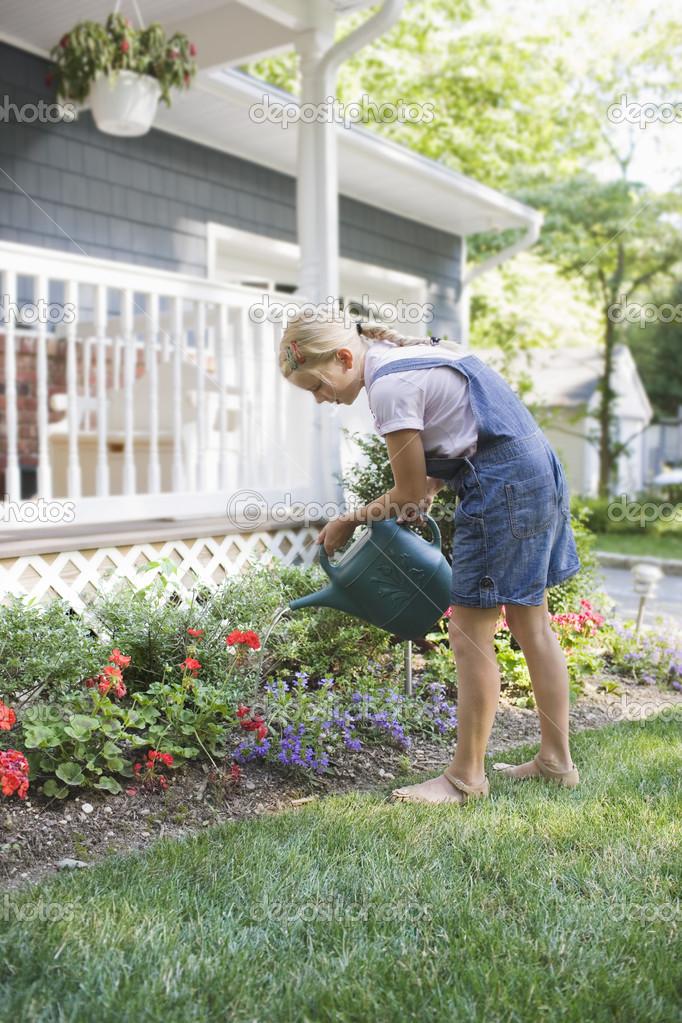 preteen Girl watering flowers