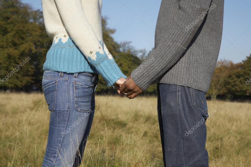 Couple standing in field holding hands
