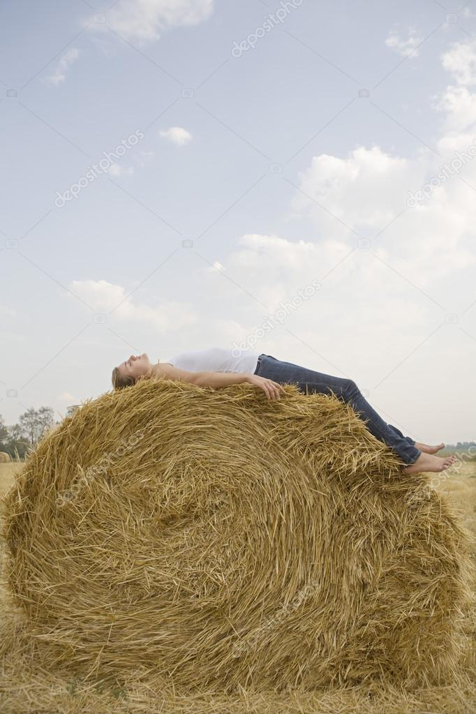 woman resting on hay bale