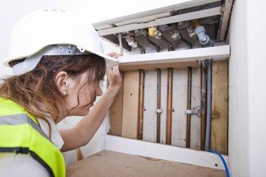 Plumber servicing central heating boiler
