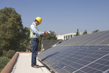 Maintenance worker stands with solar array on rooftop