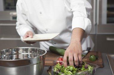 chef preparing salad at kitchen