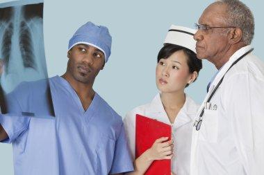 Multi ethnic doctors examining x-ray report