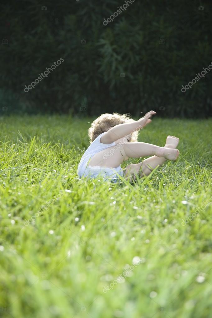 little child toppling on grass