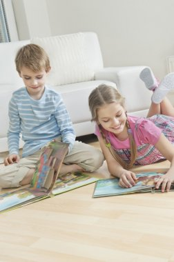 Siblings reading books on floor